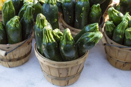 Fresh organic green zucchini squash in brown bushel baskets sitting on table at local farmers market